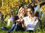 Photo of happy couple sitting in a vineyard in Niagara-on-the-Lake